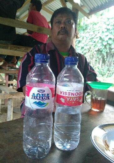 Warga menunjukkan botol Aqua dengan logo Bendera Merah Putih terbalik.