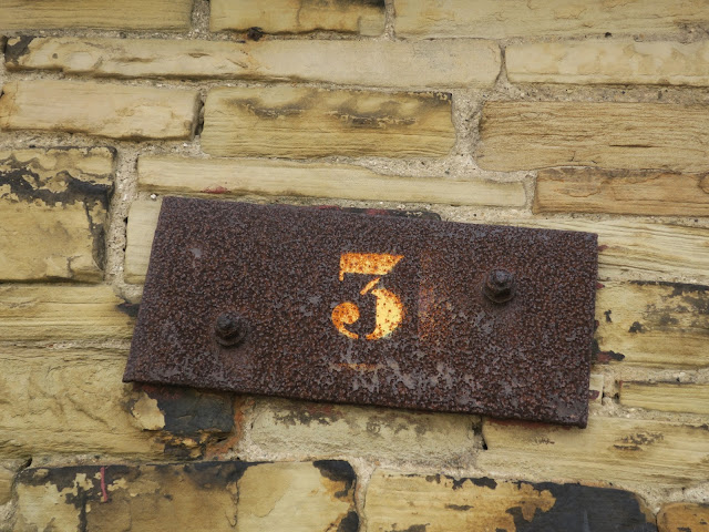 The number three on rusted metal hanging on industrial wall.