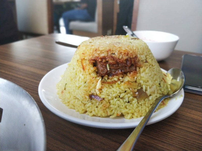 Unlike most biryanis, the classic Thalassery biryani does not use basmati rice, opting for a distinctive short grain rice called Khyma which is layered with well seasoned chicken masala (with spices like cinnamon, cardamom, cloves and nutmeg), onions, nuts, dried fruits and then sealed and slow cooked to perfection.
