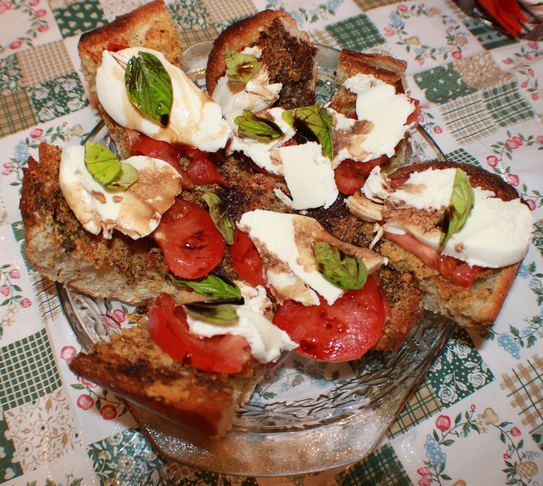 this is Italian salad on top of bread called bruschetta which originates from Rome Italy. It has tomato, cheese, basil and drizzled with olive oil and balsamic vinegar. All in a princess house crystal pie plate to catch the drippings.