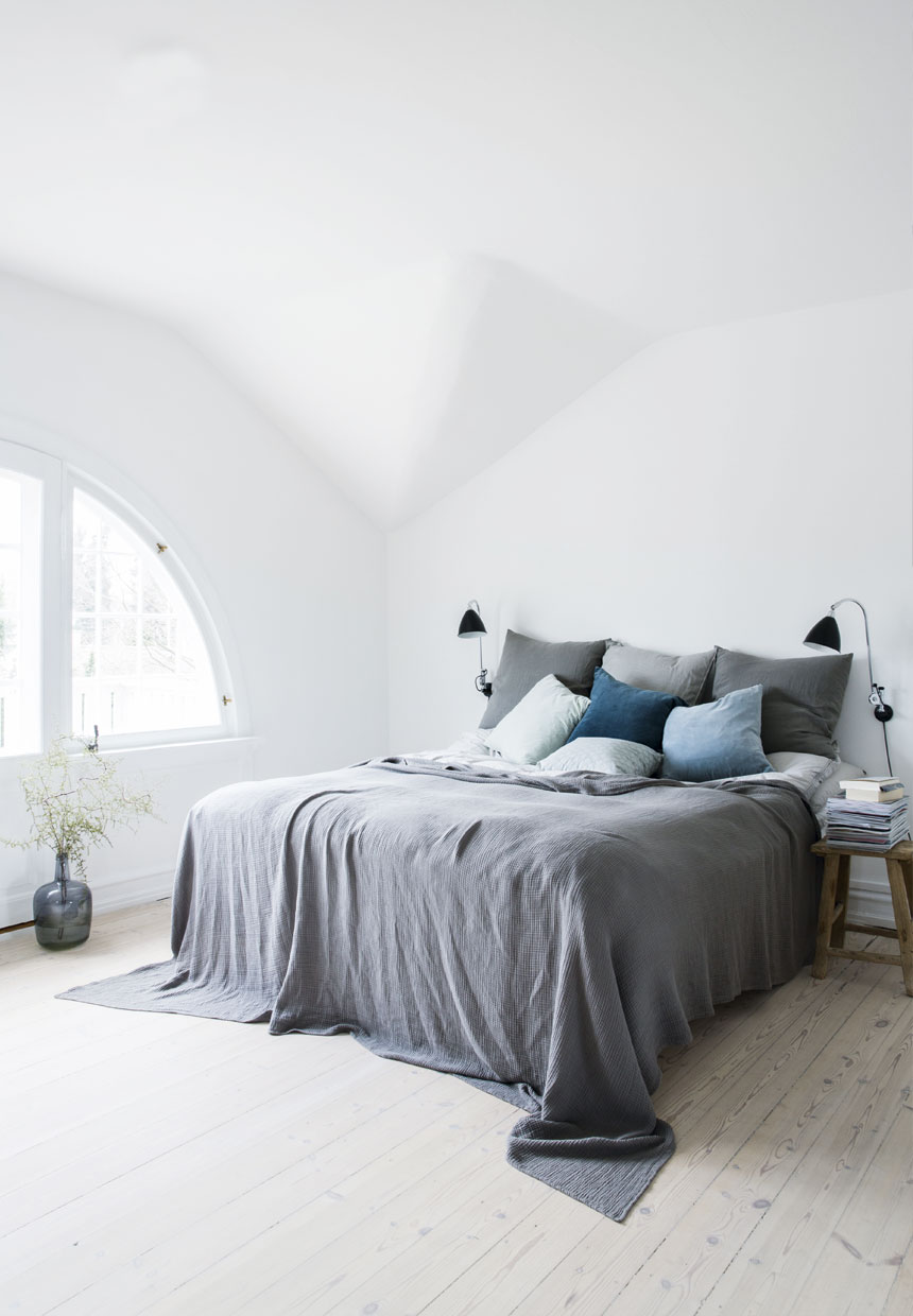Scandinavian bedroom with a grey bed sheets and blue pillows