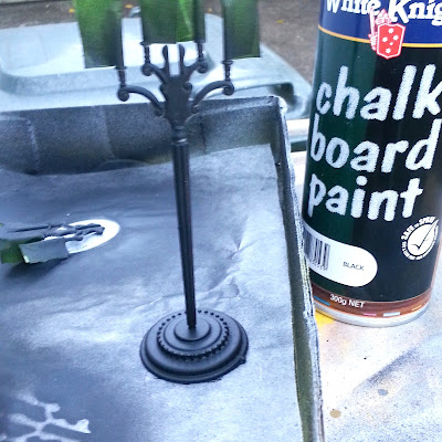 One-twelfth scale plastic candelabra pieces painted black,on a background of baking paper, with a can of chalkboard paint next to them.