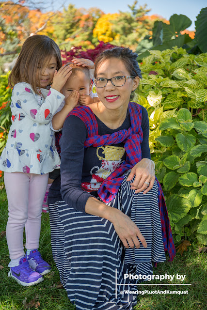 Image of a smiling tan skin bespectacled Asian woman wearing a toddler on her back in a blue and red checked woven wrap carrier. She's kneeling down in the grass surrounded by greenery and autumn foliage. The toddler on her back has her hands over her face and her older sister standing next to her is covering her head with her hands. They are being silly and playing with the sun shining through the leaves overhead.