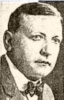 Headshot from a news clipping showing a white man with short dark hair and fine features, weaing a bow tie