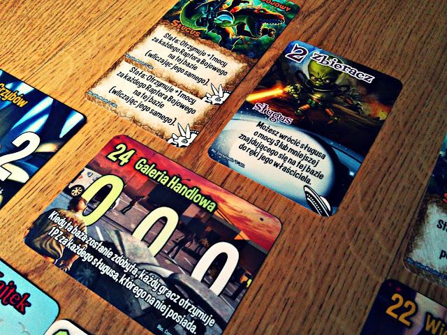 Grając w przeróżne gry RPG i MMO zawsze mieliśmy do wyboru jedną z wielu ras, którą będzie reprezentował nasz bohater. Drużyny, które formowaliśmy już w rozgrywce składały się z przeróżnych graczy i ras, jednak nigdy nie było to tak szalone jak w przypadku najnowszej gry karcianej od wydawnictwa Bard, czyli Smash Up. No bo, jak wytłumaczyć przeciwnikowi, że właśnie stracił swojego korsarza, zabitego przez dinozaura z laserowym karabinem?  Za co zapłacisz?  W solidnym, prostokątnym pudełku znajdziemy 160 kart frakcji, po 20 każda. Gracze będą wcielać się w różne potwory, magów, roboty, ninja, zombie, itd. Baz, które będziemy zdobywać w trakcie gry jest 16. Wszystkie karty są bardzo dobrej jakości, są grube i czytelne. Całość estetyki dopełniają bardzo dobre ilustracje - widać, że autorzy przyłożyli się do tego elementu, dając wielu graczom frajdę już z oglądania grafik. Instrukcja jest napisana specyficznym językiem, lekko młodzieżowym, ale bez zbędnej przesady. Młodzieżowy klimat można wyczuć również na ilustracjach - dinozaury z karabinami? Zombie? Geecy dobrze wiedzą o czym mówię. SCD wynosi 99,95 zł, co jest zbyt wygórowaną ceną w stosunku do zawartości.    Zasady  Smash Up ma bardzo proste zasady. Dobieramy dwie talie frakcji, dokładnie tasujemy i możemy zaczynać. Na środku stołu wykładamy karty baz do zdobycia równe liczbie graczy plus jedną dodatkową i rozpoczynamy rzeź. Każdy z graczy bierze 5 kart na rękę, wykłada jednego sługusa i akcję jeśli ma na to ochotę, rozpatruje wynik akcji, a tura przechodzi na następnego gracza. Każda z baz ma pewną wartość punktową - jeśli zostanie ona wyrównana lub siła wszystkich sługusów przekroczy jej wartość, uważa się ją za zdobytą. Podliczamy punkty sił wszystkich sługusów, a gracz, który ma jej najwięcej, wygrywa i zgarnia nagrodę za pierwsze miejsce. Gramy tak, do momentu gdy jeden z zawodników zdobędzie 15 punktów.       To ja dobiorę dwie dodatkowe karty..  Umiejętności poszczególnych frakcji w Smash Up dobrze odzwierc