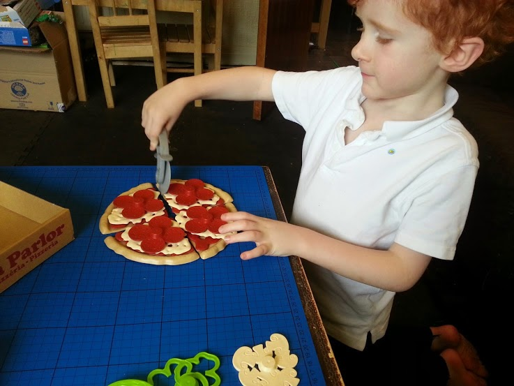 Green Toys 100% recycled plastic toy Pizza Parlour Review boy cutting pizza