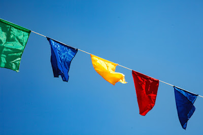 Line of multicoloured event bunting against blue summer sky