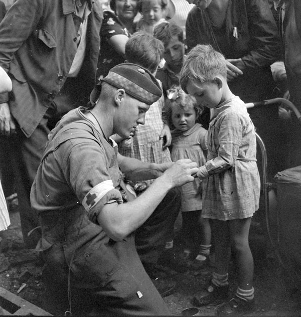 Private G-R_MacDonald-Toronto Scottish Regiment MG- giving first aid to  injured French boy-Brionne France- Aug 25 1944