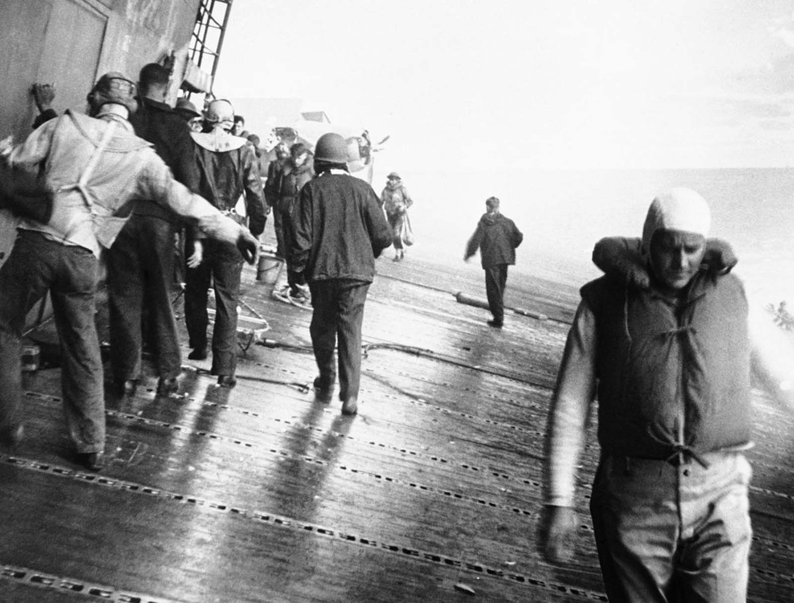 Crewmen of the USS Yorktown pick their way along the sloping flight deck of the aircraft carrier as the ship listed heavily, heading for damaged sections to see if they can patch up the crippled ship, in June of 1942.