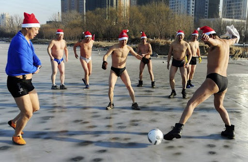Chinese Santas play footie on frozen lake