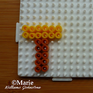 yellow and brown beads on white peg board