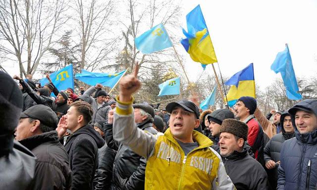 Tártaros da Crimeia protestam com bandeiras ucranianas, além da própria.