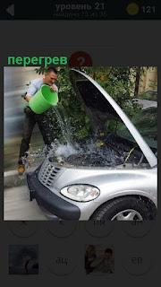 Открыт капот машины и водитель от перегрева выливает воду на мотор из ведра