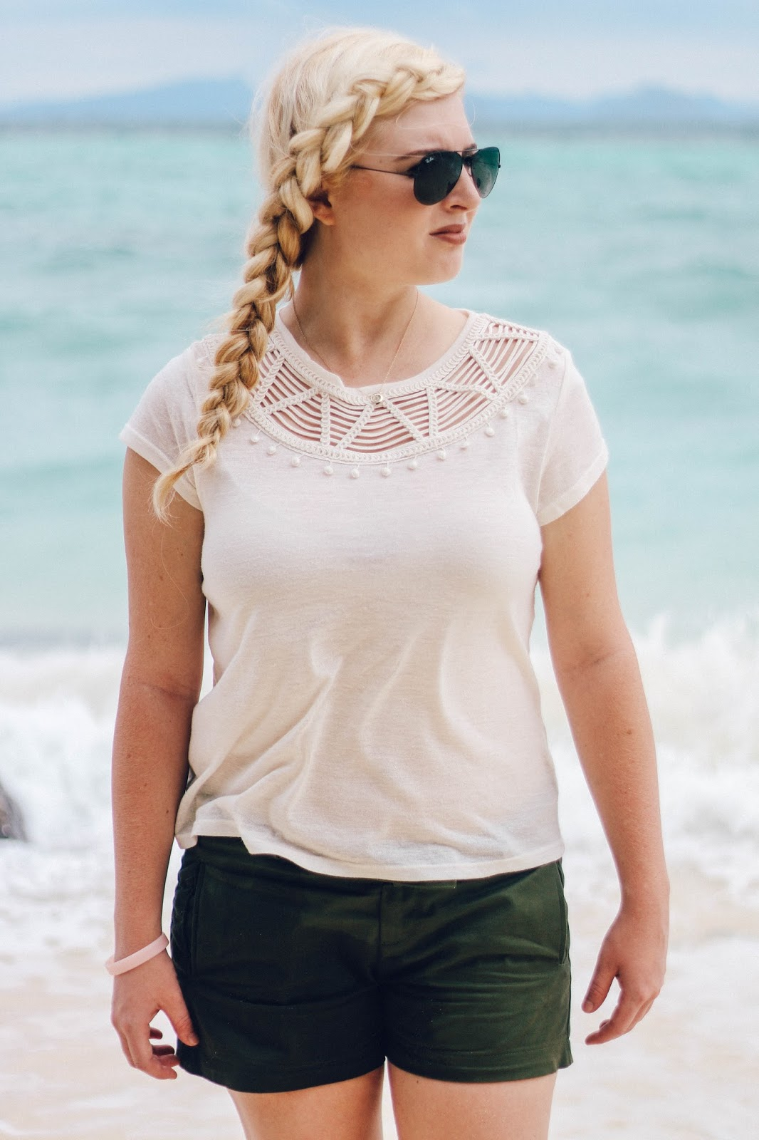 Fashion and Travel Blogger GlobalFashionGal (Brianna Degaston) styling a side french braid while wearing a white boho top and black RayBan aviators at Bamboo Island in the Phi Phi Islands, Thailand.