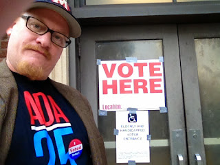 Man in ADA shirt stands by a Vote Here sign