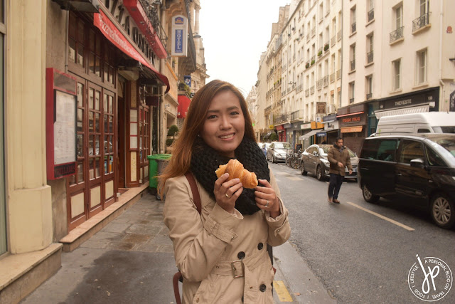 woman eating croissant on street