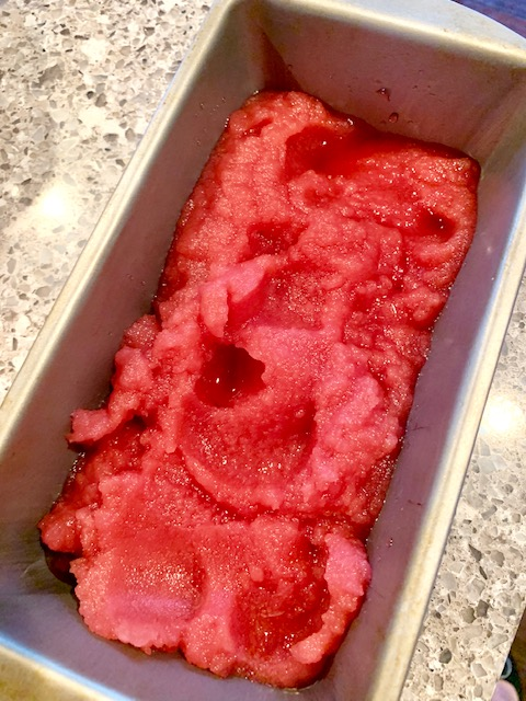 Bright pink pomegranate sorbet in a loaf pan.