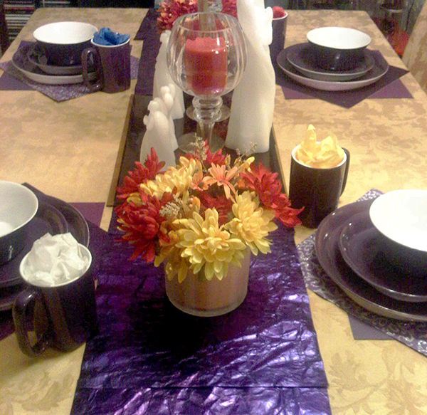 Thanksgiving table setting 4 purple plates, saucers, bowls and mugs with purple scrapbook paper for place mats and table runner