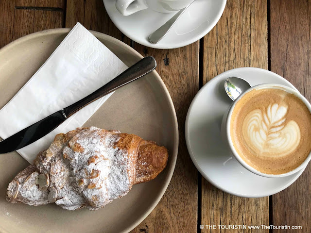 Almond croissant and a flat white espresso drink on a wooden table