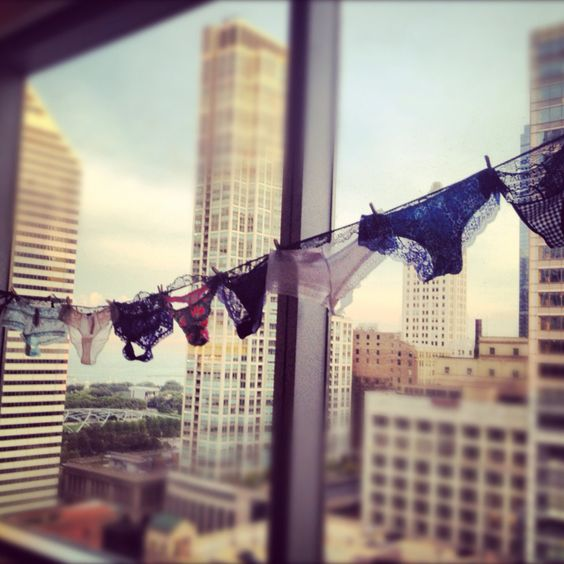 Panties on an indoor clothesline by a high-rise window.