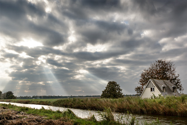 Ouse Washes in Cambridgeshire with shafts of sunlight through clouds