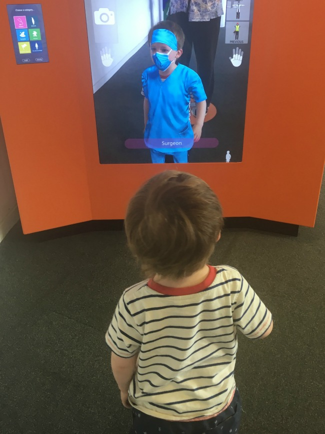 Techniquest-Virtual-Reality-changing-room-a-toddler-explores-toddler-stood-in-front-of-screen-dressed-as-a-surgeon