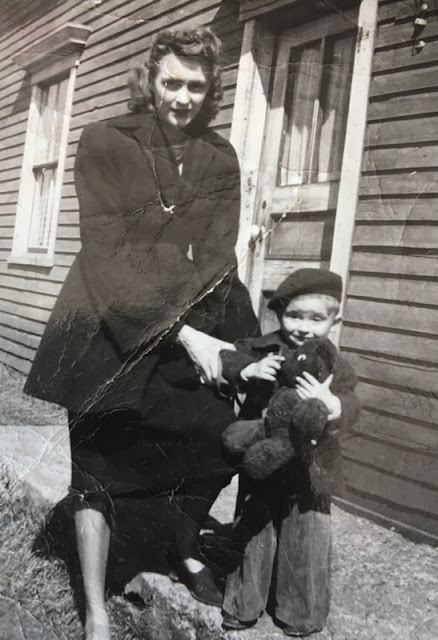 woman and small boy clutching a teddy bear, taken in the 1940's