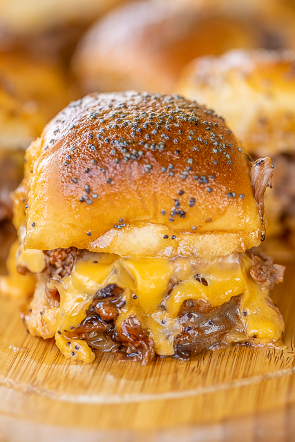 Beef & Cheddar Sliders - perfect for watching football, parties or a quick lunch and dinner. Seriously delicious!!  Hawaiian rolls, deli roast beef, bbq sauce, cheddar cheese, butter, dijon mustard, worcestershire, brown sugar and poppy seeds. Can assemble ahead of time and bake when ready to serve. You might want to double the recipe - these don't last long in our house! #sliders #superbowl #tailgating