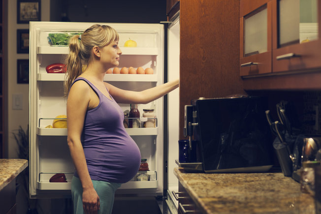 pregnant women beside refrigerator