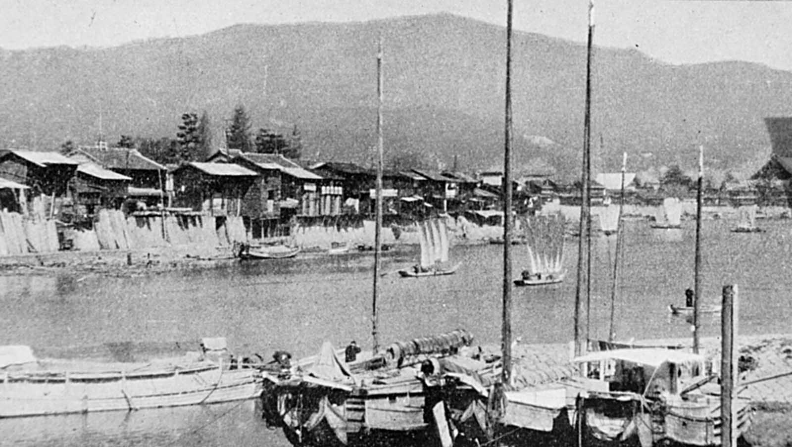 Looking north from the vicinity of the Aioi Bridge (the central T-shaped bridge targeted by the bomb). Wooden houses line the bank of the Otagawa, with traditional Japanese river boats in the foreground.