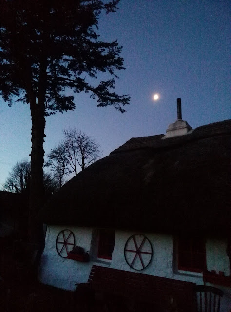 thatched cottage  in the semi darkness, blue sky, moon