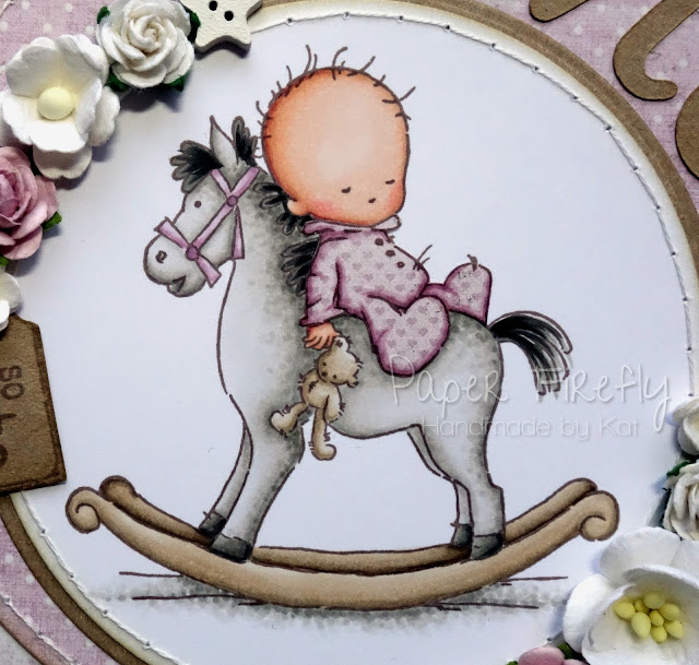 Circular pink baby girl card with baby on rocking horse (image from LOTV)