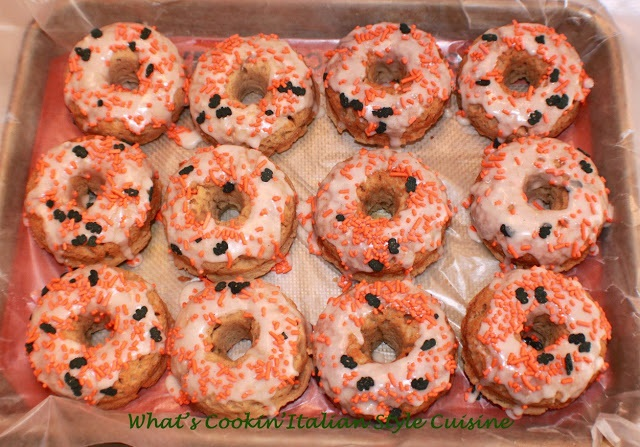 These are a baked donut with frosting on them and Halloween sprinkles. The are in a box of 12 donuts drying on wax paper. This is a recipe on how to make apple cider donuts with small pieces of chopped apples in them. The sprinkles are bats and orange sprinkles