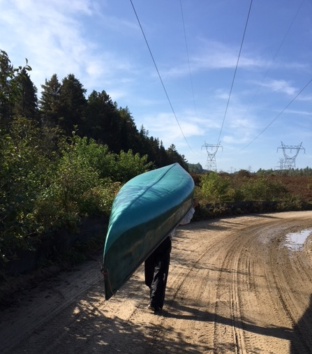 man portaging a canoe down a dirt road