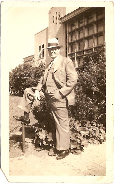 man in business suit hat glasses standing in front of multi story building in 1930s