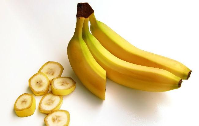 Banane intere e a pezzi su fondo bianco