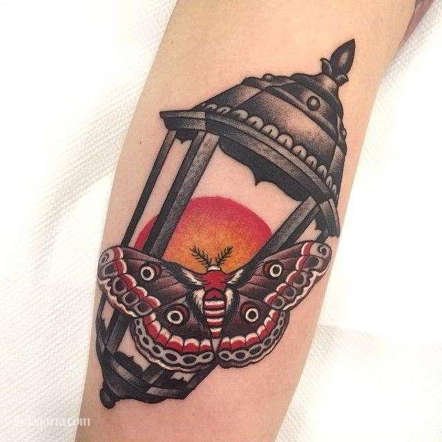 Un tatuaje de farol antiguo con una polilla