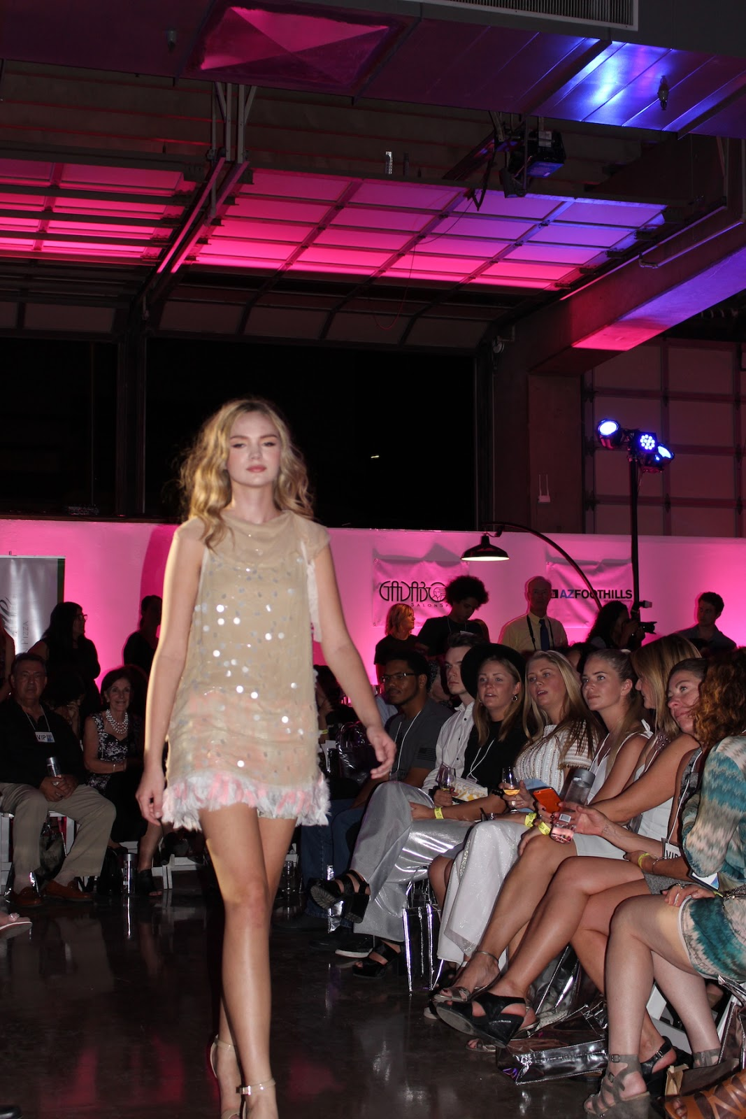 In this photo, the blonde model is walking down the runway in a tan cocktail dress.