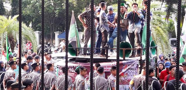Puluhan demonstran yang tergabung dalam Pengurus Besar Himpunan Mahasiswa Islam (PB HMI) berunjukrasa di depan kantor Komisi Pemilihan Umum (KPU) Pusat di Jalan Imam Bonjol Menteng, Jakarta pada Jumat (17/5). Mereka mempertanyakan kejanggalan banyaknya petugas KPPS yang sakit dan meninggal dunia. Muhammad/Bagus.co.