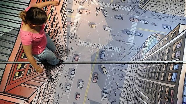 Bir bayanın gökdelenler üzerinde gerili bir ipte yürüyormuş gibi görünmesine neden olan kaldırım sanatı resmi