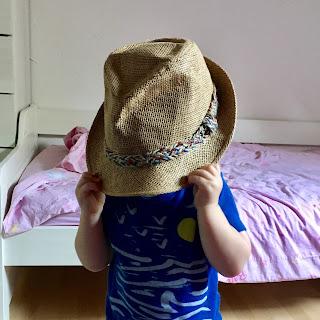 enfant caché sous un deuxième chapeau