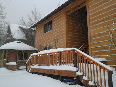 Exterior photo of condos with snow falling, six inches of snow and lights shining along the deck railing.