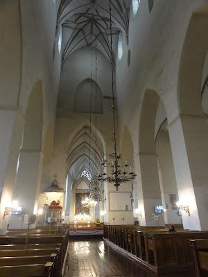 En høy, hvelvet kirkesal med lyskroner ned fra taket.