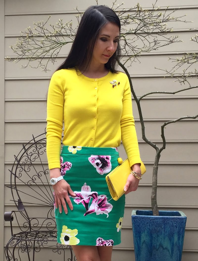 Wearing a bright yellow cardigan with 2 ladybug pins and a floral pin, tucked into a green floral print skirt. Holding a bright yellow clutch and wearing pink bow sandals and a white watch.