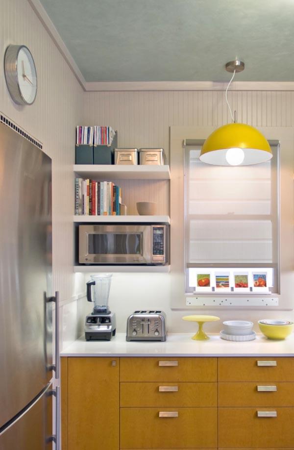 cozinha com prateleira livros culinaria expostos armarios em madeira amarelada eletrodomesticos inox
