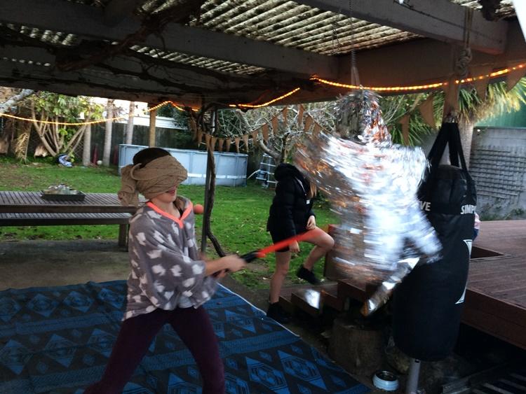 birthday girl takes a swing at the pinata