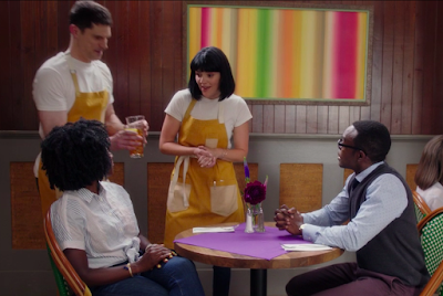 A tall white man with short brown hair and a short white woman with a black bob haircut are standing by Chidi and Simone's table, wearing white t-shirts and yellow aprons. Chidi and Simone sit across a table from each other.