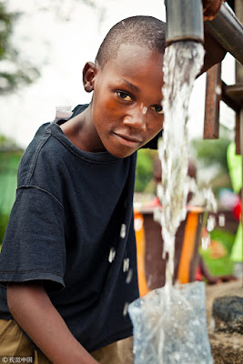 Africa boy is smiling at camera and using water