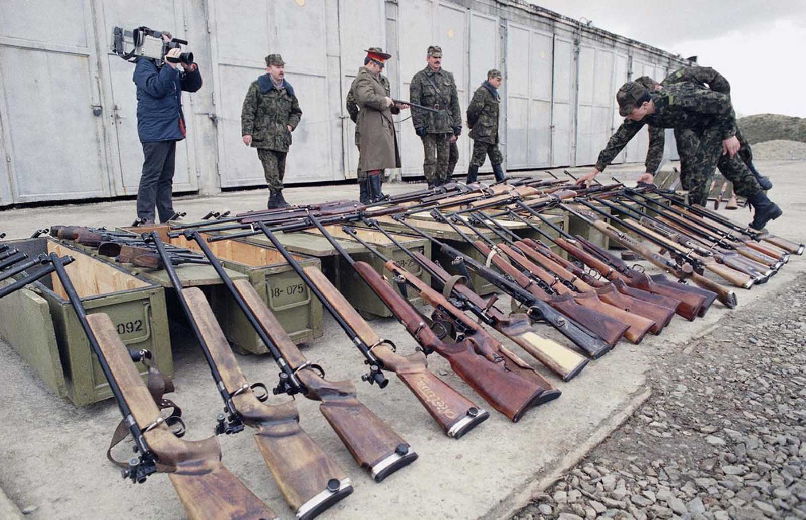 Two Soviet paratroopers inspect weapons confiscated from a local militia organization in Kaunas, Lithuania on Sunday, March 26, 1990. Soviet President Gorbachev ordered all Lithuanians to surrender their firearms to Soviet authorities.