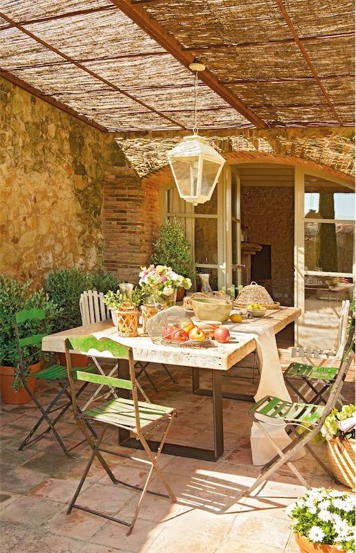 porche rustico con techo de cañizo y sillas de hierro verde chicanddeco